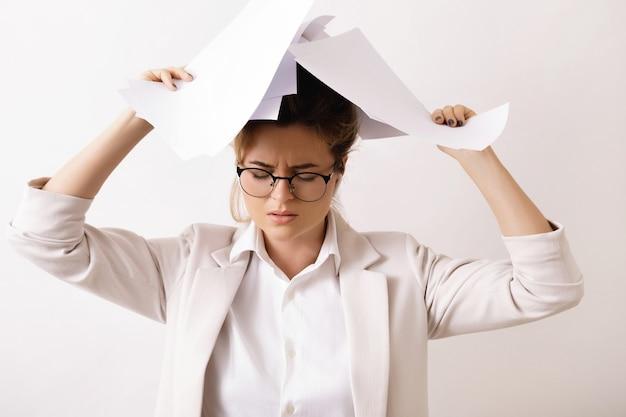 Zmęczona biznesowa kobieta z dużą ilością papierowych dokumentów. pojęcie przepracowania i nadgodzin.