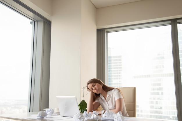 Zmęczona bizneswoman nieproduktywna, by skończyć pilną pracę, za dużo papierkowej roboty
