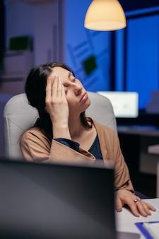 Zmęczona bizneswoman trzymając zamknięte oczy pocierając czoło, ponieważ jest wyczerpująca. pracownik zasypiający samotnie do późnych godzin nocnych w biurze dla ważnego projektu firmy.