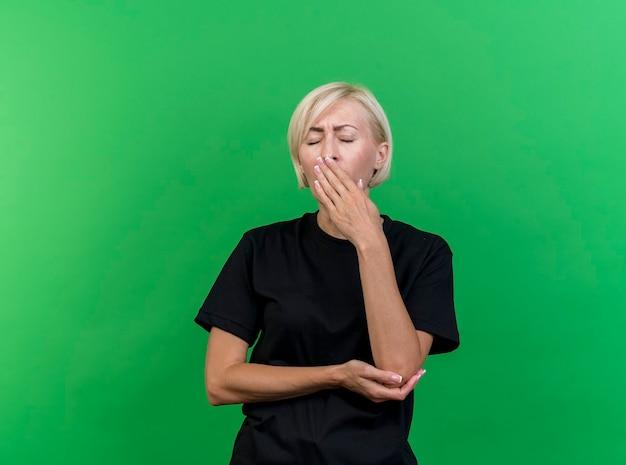 Zmęczona blond słowiańska kobieta w średnim wieku kładąca rękę pod łokciem ziewająca trzymając dłoń na ustach z zamkniętymi oczami odizolowana na zielonym tle z przestrzenią do kopiowania