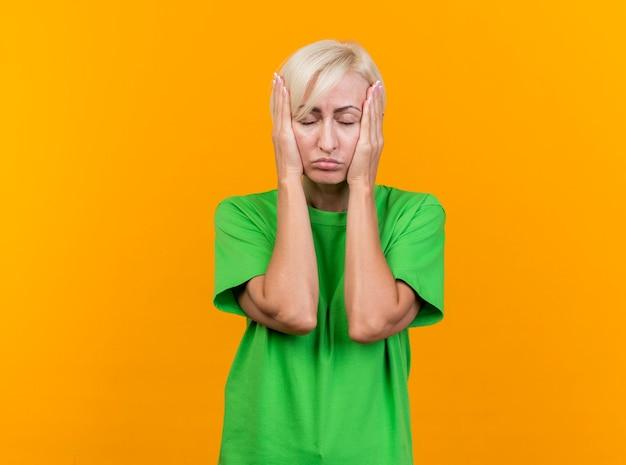 Zmęczona blondynka słowiańska blondynka w średnim wieku kładzie ręce na twarzy z zamkniętymi oczami na białym tle na żółtej ścianie z miejsca na kopię