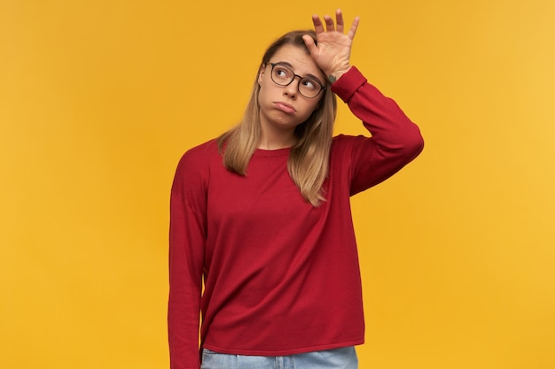 Zmęczona blondynka w okularach z wypukłymi policzkami, patrząc w lewy górny róg, stojąc tyłem dłoni w pobliżu czoła na białym tle