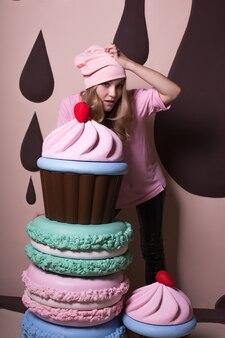 Zmęczona blondynka w różowej czapce i koszulce bawi się dużymi makaronikami i babeczkami w studio