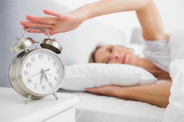 Zmęczona blondynki kobieta obraca daleko jej alarm w ranku