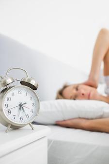 Zmęczona blondynki kobieta zakrywa jej ucho od budzika hałasu w łóżku
