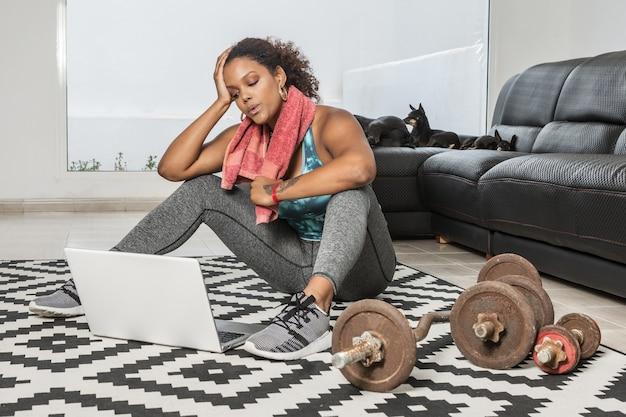 Zmęczona czarna lekkoatletka z ręcznikiem na szyi, siedząca na podłodze i opierając się na dłoni podczas odpoczynku po intensywnym treningu w domu i oglądaniu wideo na laptopie