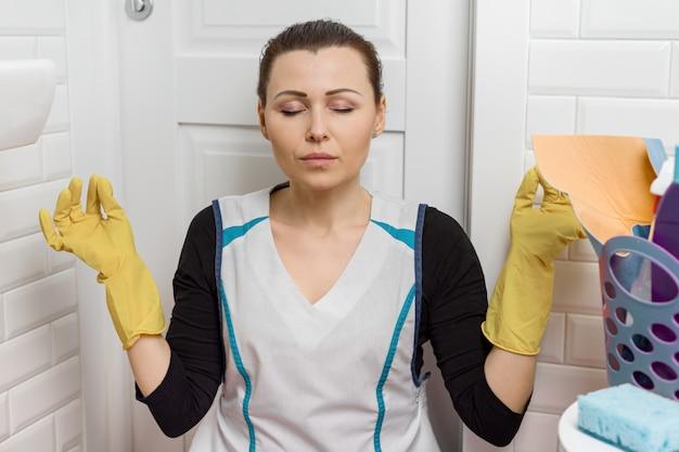 Zmęczona dorosła kobieta sprzątanie pokoju wc łazienka, kobieta zamyka oczy, medytuje, odpoczywa.