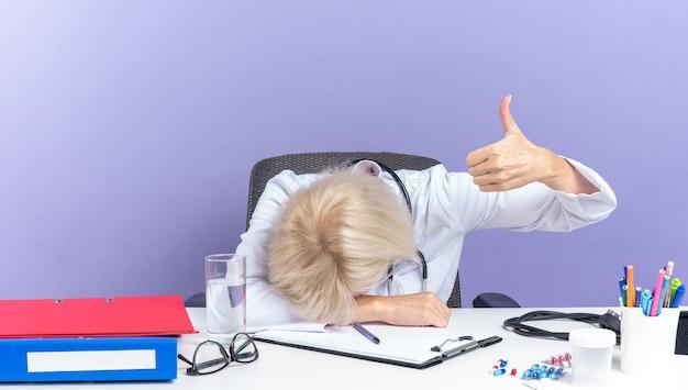 Zmęczona dorosła lekarka w szacie medycznej ze stetoskopem siedząca przy biurku z narzędziami biurowymi kładąca głowę na biurku i kciukiem odizolowana na fioletowej ścianie z kopią miejsca