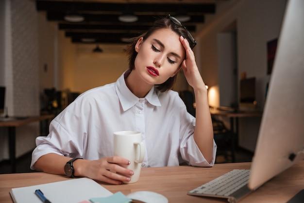 Zmęczona dziewczyna biurowa. ręka blisko twarzy