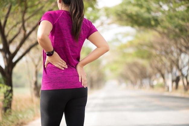 Zmęczona dziewczyna odczuwa ból pleców i bioder podczas ćwiczeń, koncepcja opieki zdrowotnej.