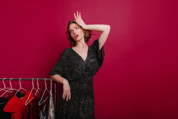 Zmęczona dziewczyna pozuje w garderobie i patrząc w górę