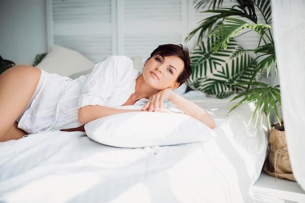 Zmęczona dziewczyna relaksuje się w łóżku tylko w hotelu