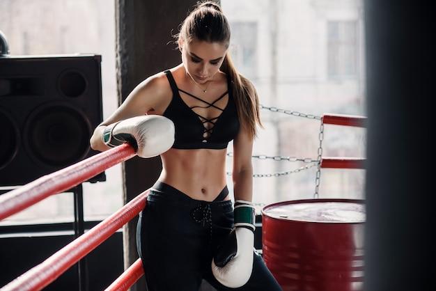 Zmęczona dziewczyna sportowa oparła się na czerwonych linach na ringu i odpoczęła po ciężkim treningu w czarnej sali gimnastycznej. pojęcie zdrowego i sportowego stylu życia.