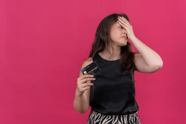 Zmęczona dziewczynka kaukaski w czarnym podkoszulku trzyma kartę bankową i położyła dłoń na czole na różowym tle