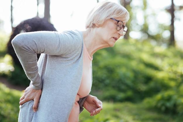 Zmęczona emerytka, starzejąca się kobieta dotykająca pleców i odczuwająca ból stojąc w parku