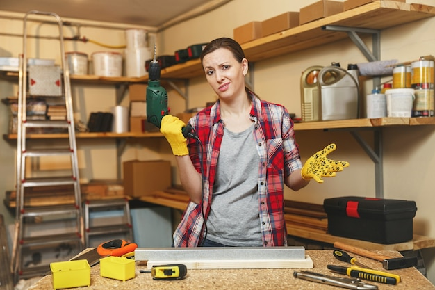 Zmęczona gaga kaukaska młoda brązowowłosa kobieta w kraciastej koszuli i szarej koszulce, pracująca w warsztacie stolarskim przy stole, wiercąca otworami w kawałku żelaza i drewnie podczas robienia mebli.