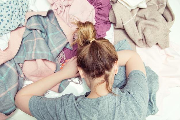 Zmęczona gospodyni domowa leży w rozpaczy na stercie wypranych ubrań. rutyna domowa, życie codzienne.