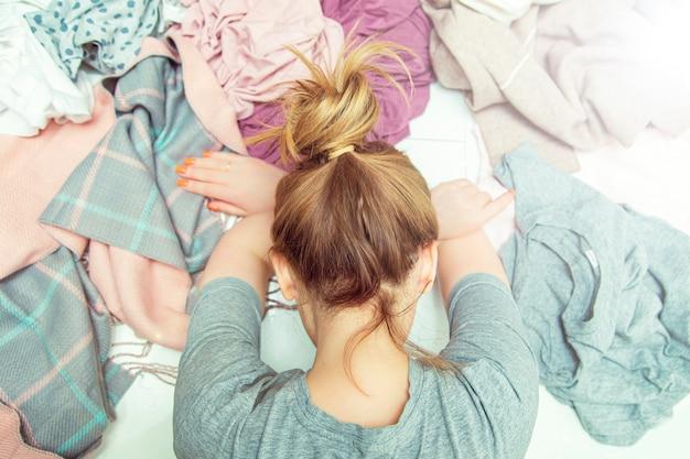 Zmęczona gospodyni domowa leży w rozpaczy na stosie wypranych ubrań. rutyna domowa, życie codzienne.