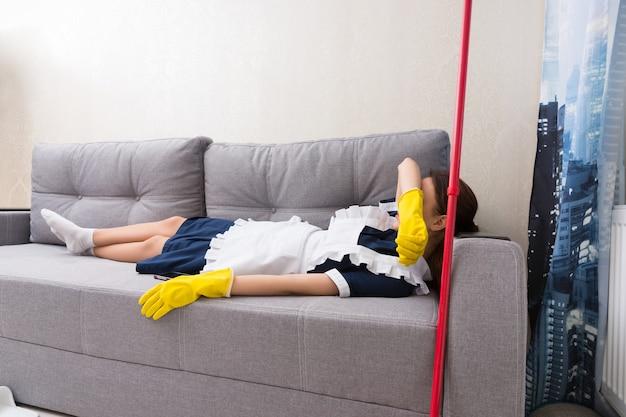 Zmęczona gospodyni lub pokojówka w mundurze odpoczywa w pracy leżąc na kanapie zasłaniając oczy podczas drzemki z mopem obok