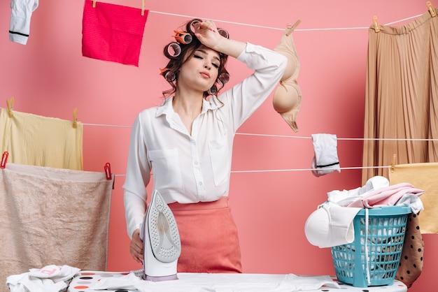 Zmęczona gospodyni młoda kobieta w koszuli, ubrania na liny i prasowanie czystych ubrań na pokładzie robi prace domowe na białym tle na różowej ścianie