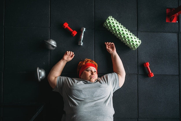 Zmęczona gruba kobieta leży na podłodze w siłowni. spalanie kalorii, otyła kobieta w klubie sportowym