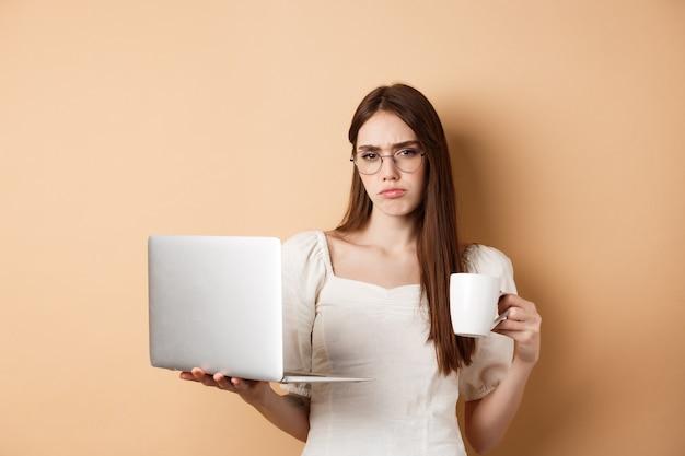 Zmęczona i niechętna dziewczyna nienawidzi pracy, picia porannej kawy i korzystania z laptopa, marszczy brwi i zdenerwowanie, stojąc na beżowym tle.