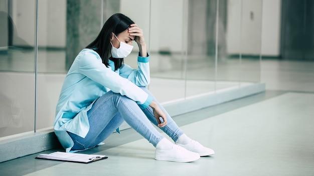 Zmęczona i nieszczęśliwa młoda kobieta lekarz w masce medycznej bezpieczeństwa w stresie po nieudanej pracy