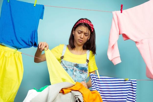 Zmęczona i piękna gospodyni domowa na białym tle na niebieskim tle. młoda kobieta kaukaski otoczona przez umyte ubrania. życie domowe, jasne dzieła sztuki, koncepcja sprzątania. wygląda na zdenerwowanego.
