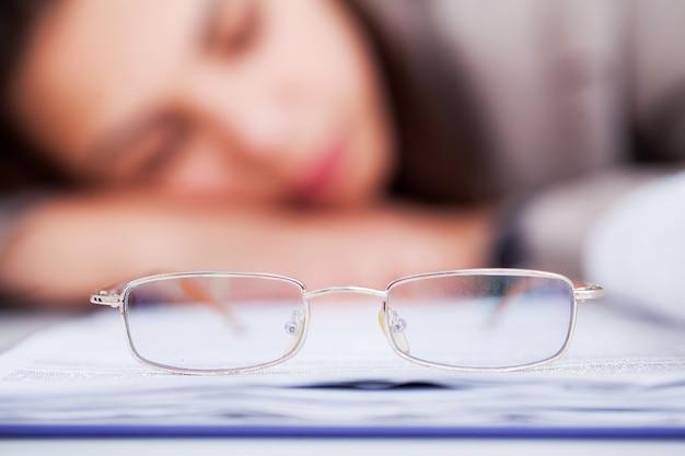 Zmęczona i przepracowana kobieta spanie w pracy