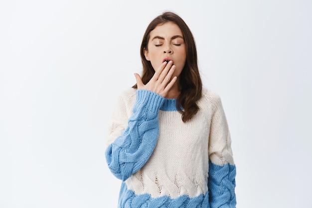 Zmęczona i śpiąca dziewczyna ziewająca z zamkniętymi oczami i otwartymi ustami, znudzona, stojąca w swetrze pod białą ścianą