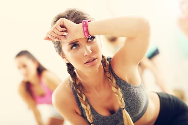 Zmęczona i spocona, ale zadowolona kobieta po treningu na siłowni