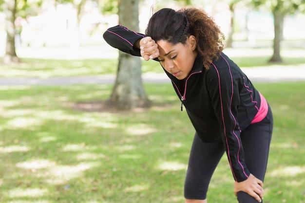 Zmęczona kobieta bierze przerwę podczas gdy jogging w parku