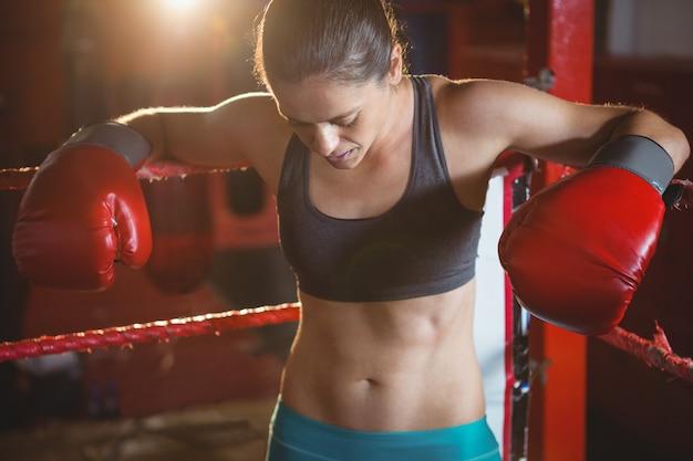 Zmęczona kobieta bokser opierając się na ringu