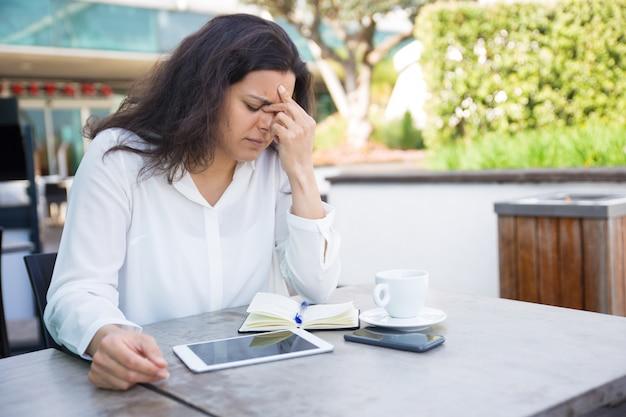 Zmęczona kobieta dotykając nosa mostu i siedząc w kawiarni ulicy