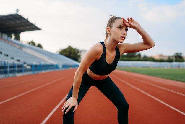 Zmęczona kobieta jogger w odzieży sportowej, trening na stadionie. kobieta robi ćwiczenia rozciągające przed bieganiem na arenie na świeżym powietrzu