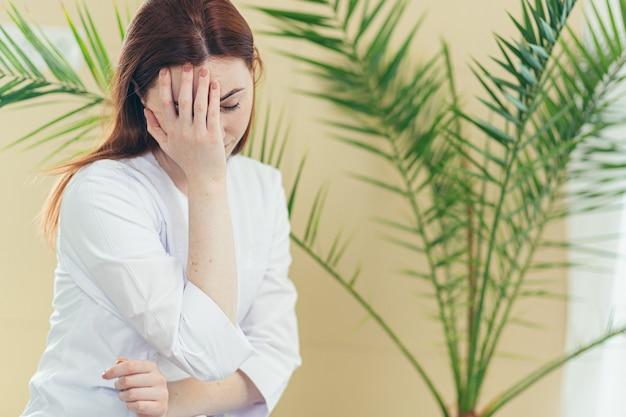 Zmęczona kobieta lekarz pracownica po ciężkim dniu w klinice