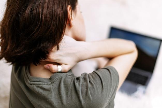Zmęczona kobieta masuje otarcie sztywnego bólu szyi