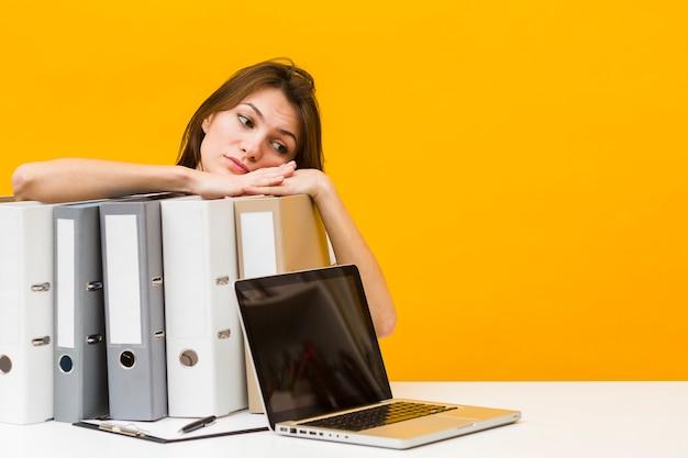 Zmęczona kobieta odpoczywa głowę na segregatorach przy biurkiem