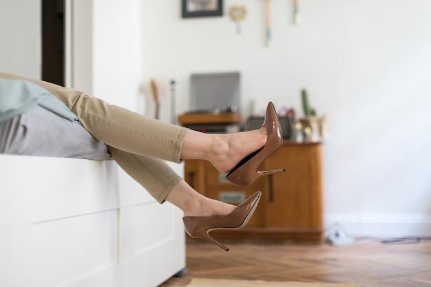 Zmęczona kobieta odpoczywa zdejmując brązowe buty na wysokim obcasie po pracy lub spacerze, leżąc na sofie. niewygodne buty