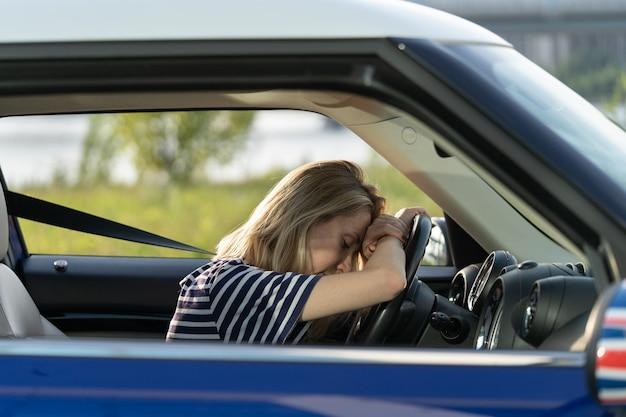 Zmęczona kobieta opiera się na kierownicy w samochodzie prowadząca nieszczęśliwa śpiąca kobieta-kierowca stara się nie zasnąć