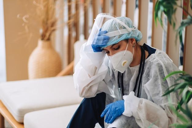 Zmęczona kobieta pielęgniarka pracownik szpitala lekarz chirurg w odzieży ochronnej patrząc na smutek po ciężkim dniu pracy lub operacji.