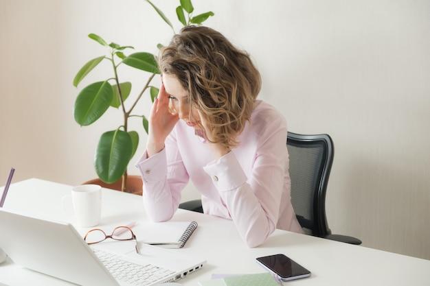 Zmęczona kobieta położyła głowę na stole. zmęczona kobieta z migreną podczas gdy siedzący przy jej pracującym miejscem w biurze. przepracowany bizneswoman. sfrustrowana młoda kobieta trzymając oczy zamknięte