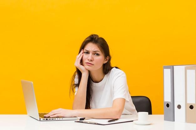 Zmęczona kobieta pozuje przy jej biurkiem z laptopem