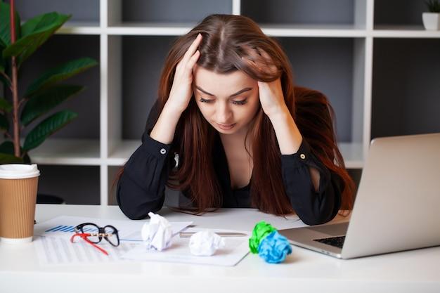 Zmęczona kobieta pracuje przy komputerem w biurze