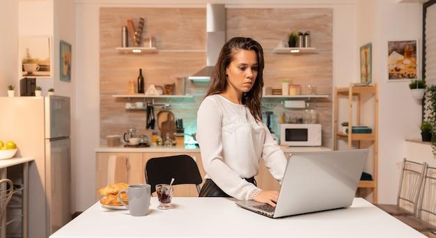 Zmęczona kobieta pracuje w godzinach nadliczbowych późno w nocy za pomocą laptopa w domowym biurze. skoncentrowany przedsiębiorca w domowej kuchni korzystający z notebooka w późnych godzinach wieczornych.