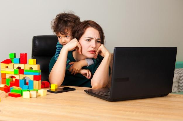 Zmęczona kobieta przy laptopem pracuje w domu. chłopiec, dziecko zbudował dom z kostek i wisi na szyi matki, domagając się uwagi.