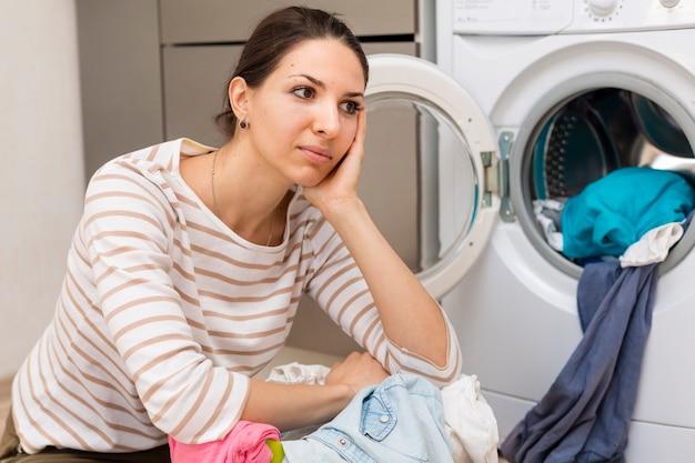 Zmęczona kobieta robi pranie