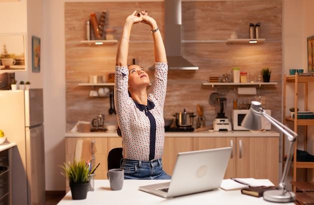 Zmęczona kobieta rozciąga się podczas pracy w godzinach nadliczbowych z domowej kuchni. pracownik korzystający z nowoczesnych technologii o północy wykonujący nadgodziny w pracy, firmie, zajęty, karierze, sieci, stylu życia, bezprzewodowo.