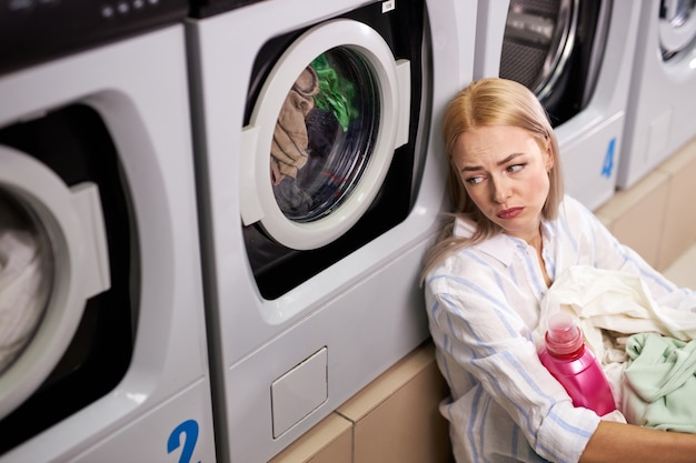 Zmęczona kobieta siedzi obok pralek i patrzy w górę ze smutkiem. kaukaska kobieta spędziła czas na praniu, czekaniu i znudzonej kobiecie z brudnymi ubraniami w koszu