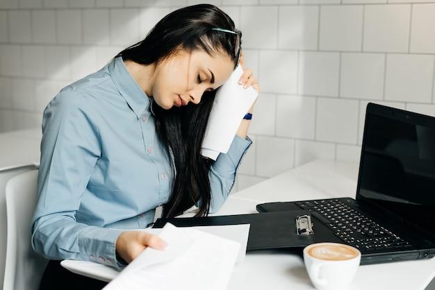 Zmęczona kobieta siedzi przy biurku w biurze